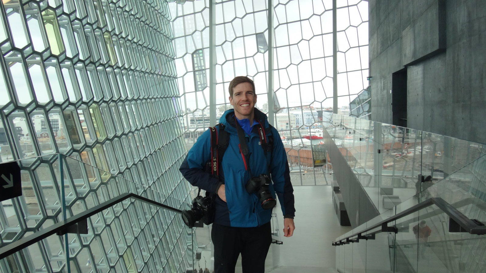 Chad Baumer, man with camera around his neck in a glass room