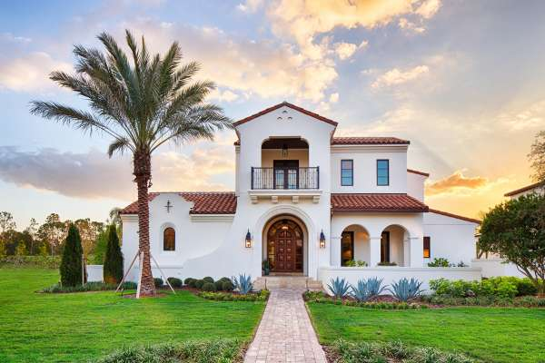 Spanish style building with palm tree on lush green grass