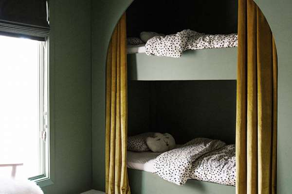 Green arched bunk-bed setup with animal rug