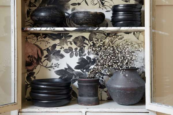 Cupboard with gray pottery against floral wallpaper