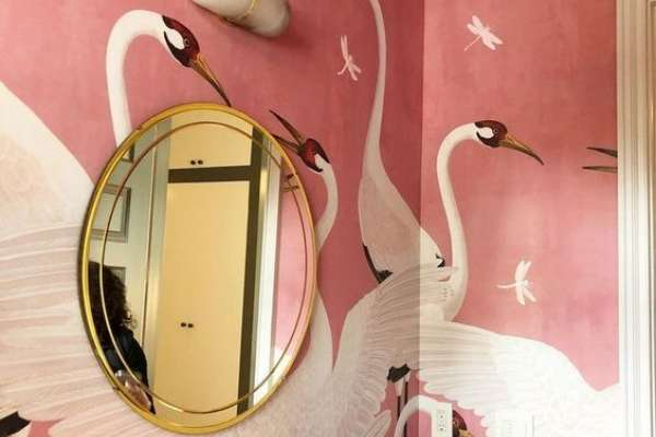 Swan mural painted on pink wall with gold circle mirror