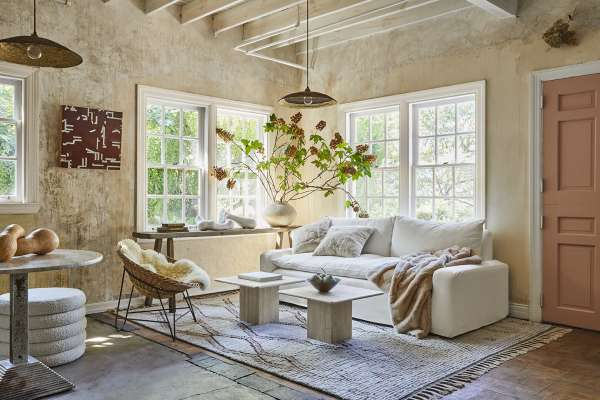 Living room with natural accents like clay wallpaper, fur blanket, and plants