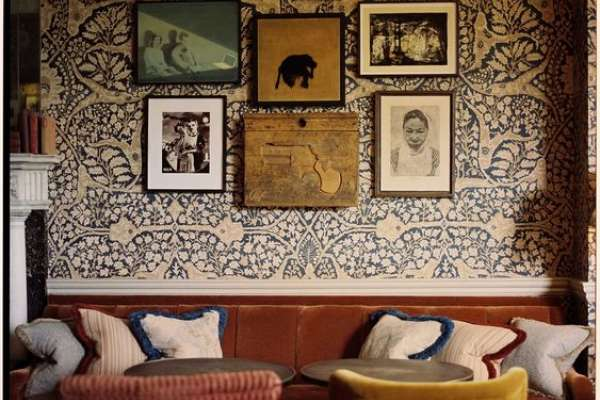 Vintage room with gallery wall, wallpaper, and velvet chairs
