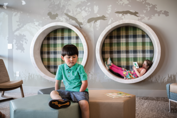 Children sitting on lounge stools in colorful children's hospital