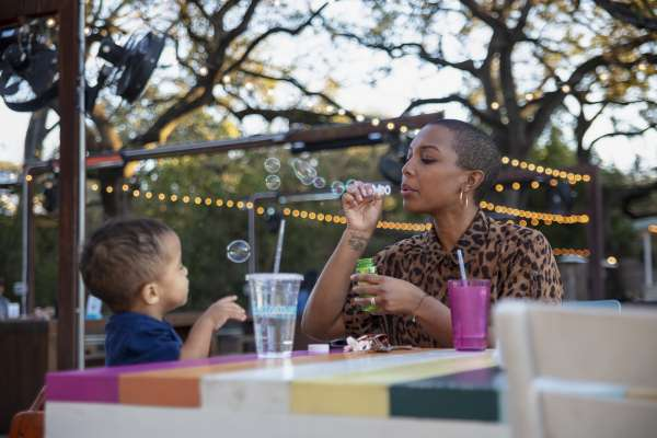Krystal Lucero blowing bubbles with her son in a park