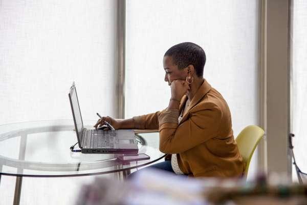 Krystal Lucero working on laptop next to window