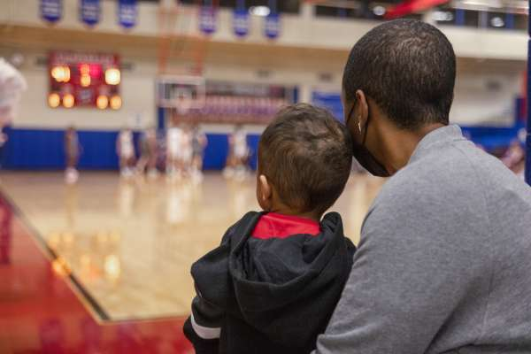 Krystal Lucero and son sitting at basketball game
