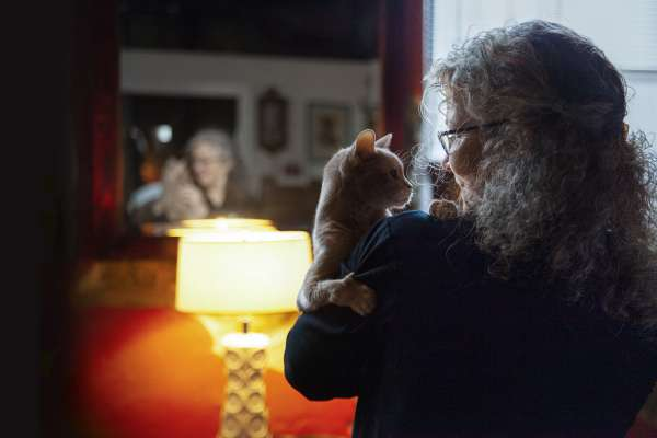 Lyn Godley at home with her cat, in front of beautiful lamp