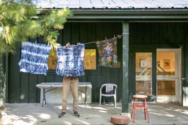 Student hanging fabric outside cabin at Ox-Bow school