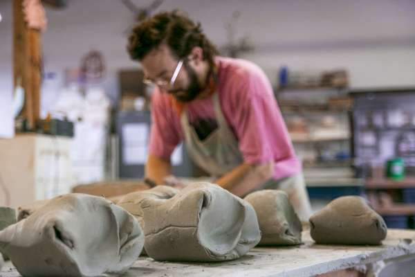 Student at Ox-Bow school crafting pottery artwork