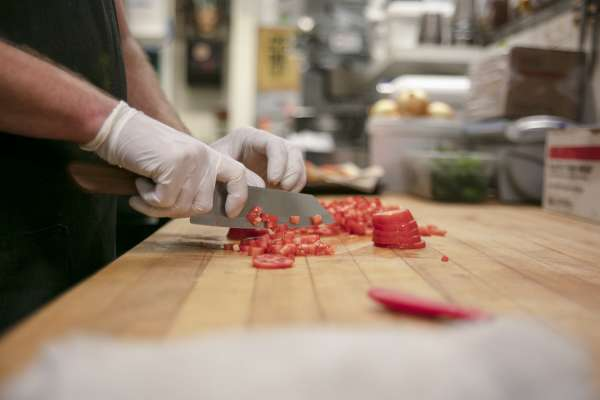 Hands chopping tomatoes for a meal at Ox-Bow school of art in Michigan