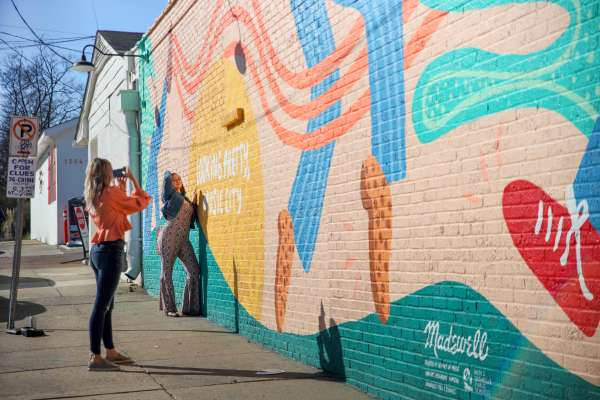 Of Note influencers posing against mural wall in Nashville, TN