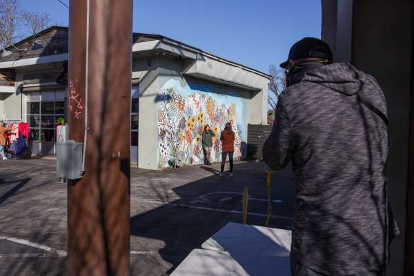 Influencers capturing photos against a mural