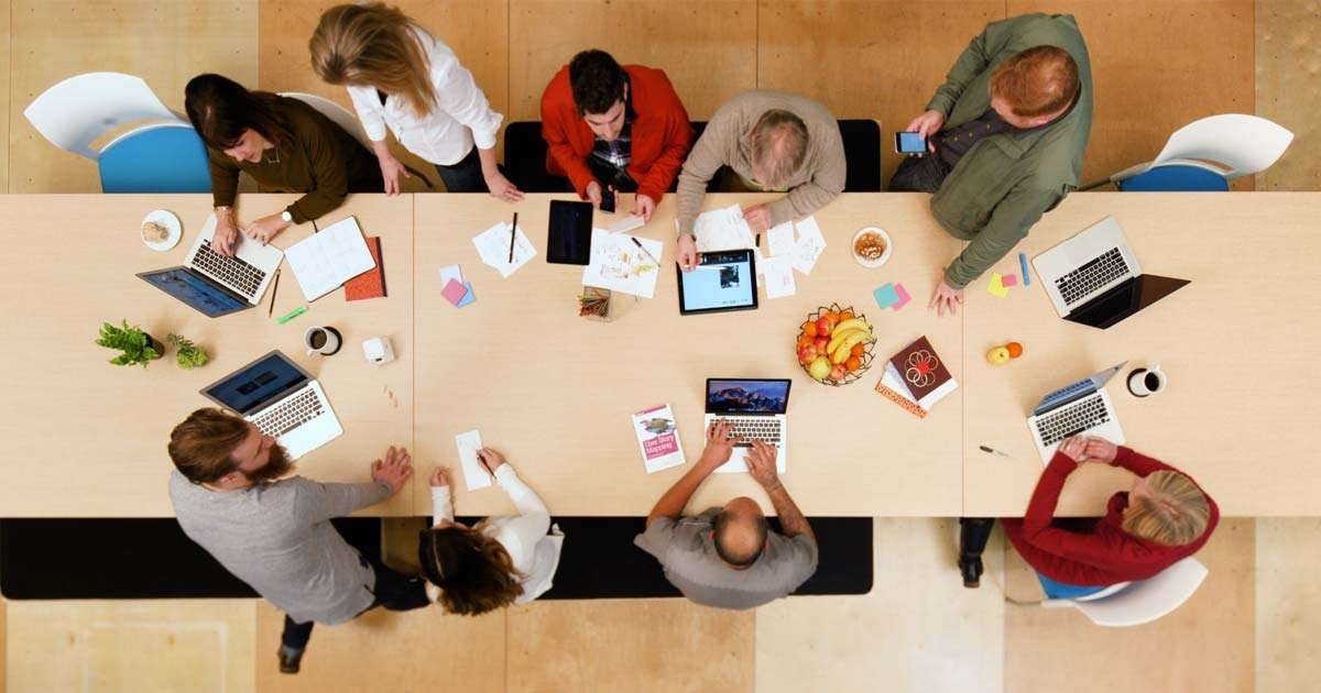 Eleven wood table from above with employees collaborating