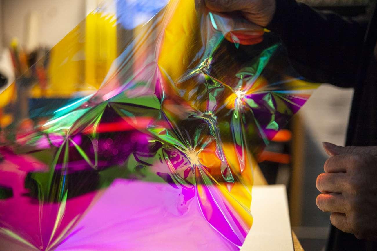 Florescent paper reflecting light as hands create art